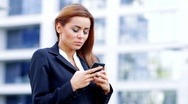 A beautiful business woman using mobile phone outside office building Stock Footage