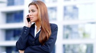 Friendly business woman using mobile phone outside office building Stock Footage