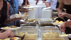 Buffet line of food with multiple people serving themselves. - stock footage