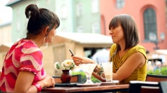 Two female friends with mobile phone in bar, outdoors, steadycam shot HD Stock Footage