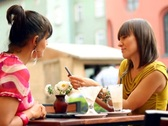 Two female friends with mobile phone in bar, outdoors, steadycam shot NTSC Stock Footage