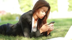 Beautiful business woman relaxing on grass with laptop and phone - stock footage