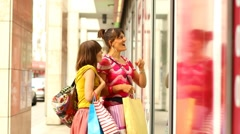 Two female friends with shopping bags looking at shop window, steadycam shot Stock Footage