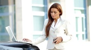 Attractive business woman using mobile phone and laptop Stock Footage