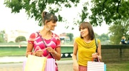 Happy female friends with shopping bags walking in the city, steadycam shot Stock Footage