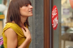 Woman looking at shop window with sales promotion, steadycam shot NTSC Stock Footage
