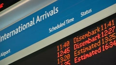 International arrivals board at airport Stock Footage