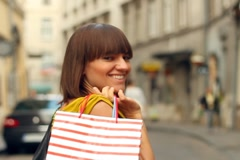 Happy woman with shopping bags walking in the city, slow motion, steadycam shot - stock footage