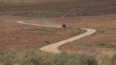 Jeep drives up dirt road from far away Stock Footage