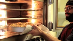 Baker taking cinnamon rolls out of the oven Stock Footage