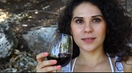 Stock Video Footage of Young pretty woman tastes and appreciates red wine