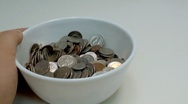 Eating coins from the bowl Stock Footage