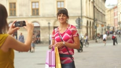 Young woman taking photo of her friend in the city, steadicam shot Stock Footage