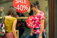 Two female friends with shopping bags looking at shopwindow, steadycam shot - stock footage