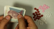 Stock Video Footage of Cambodian Riel KHR, Counting Drugs and Money, Health Care, Colorful Pills