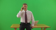 Businessman sitting on edge of desk and talking on cell phone Stock Footage