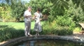 male and female feed the fish in the pond Footage