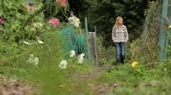 Woman walking through a community garden Stock Footage