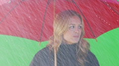 Close up of female standing under umbrella waving to taxi Stock Footage