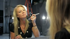 Pretty woman putting on makeup before a photo shoot Stock Footage