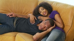 African-American man and woman laying on couch - stock footage