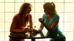 Two women standing at a table drinking wine Stock Footage