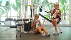Women drinking water and talking after workout - stock footage
