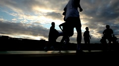 Silhouettes of  running people on the background of the sunset sky Stock Footage