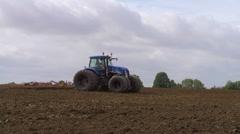 Blue tractor harrowing a field in autumn, across frame. Stock Footage