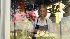 Blonde girl working in flower shop with a bunch of roses and gerbera - stock footage