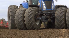 Blue tractor turning close up with a harrow 2 Stock Footage
