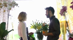 Young woman and client talking in flowers shop Stock Footage
