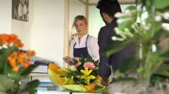 Sales manager at counter and client shopping in flowers shop - stock footage