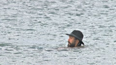 Man in Hat Swimming and Standing in Water Stock Footage