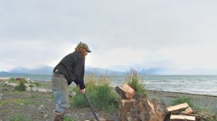 Hardy Alaskan Man Splitting Wood at Beach Stock Footage