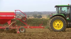 Planting the grain, tractor pulls seed drill across frame. Stock Footage
