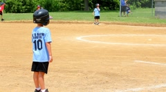 Young boy standing on third base waiting to be hit home. Stock Footage