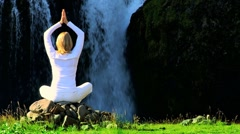 Female in White Performing Yoga by Waterfall - stock footage