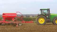 Sowing wheat, a green tractor pulls seed drill across frame. Stock Footage