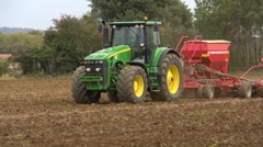 Sowing wheat, mid shot of a tractor and seed drill coming through frame. Stock Footage