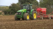 Stock Video Footage of sowing wheat, mid shot of a tractor and seed drill coming through frame.