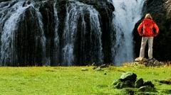 Female Hiker Reaching a Glacial Waterfall - stock footage