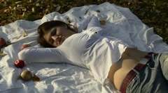 Young woman stretching on bedspread in autumn park Stock Footage