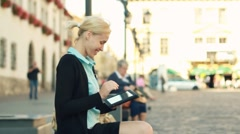Excited businesswoman with tablet computer in the city, steadycam shot - stock footage