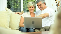 Middle Aged Couple Using Home Laptop Stock Footage
