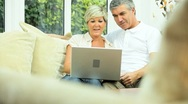 Stock Video Footage of Middle Aged Couple Using Home Laptop