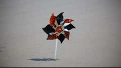 Pinwheel in the sea sand turning on the blowing wind Stock Footage
