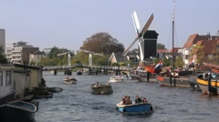 Boats in a canal with windmill in Holland Stock Footage