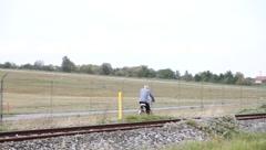 A man rides his bike along the tracks Stock Footage