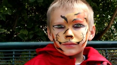 Young boy with his face painted as a tiger Stock Footage
